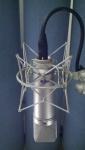 Neumann u87 condenser microphone front view with logo in spider shockmount