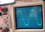 Oscilloscope readout of an amplifier output. This shows a 1 KHz sine wave clipping into 5 ohms. 10V/division.